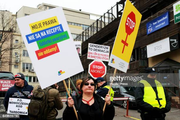 A woman stands in front of the right wing ruling government pary head quarters the Law and Justice party in Warsaw Poland on March 08 2017 during...
