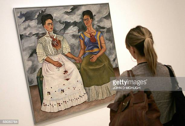A woman stands in front of 'The Two Fridas' part of the Frida Kahlo exhibition at the Tate Modern in London 07 June 2005 It is the first major...