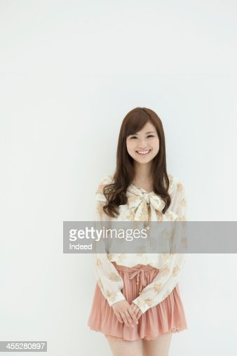 Woman stands in front of white background