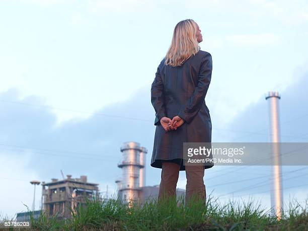 Woman stands in green grass below smokestacks