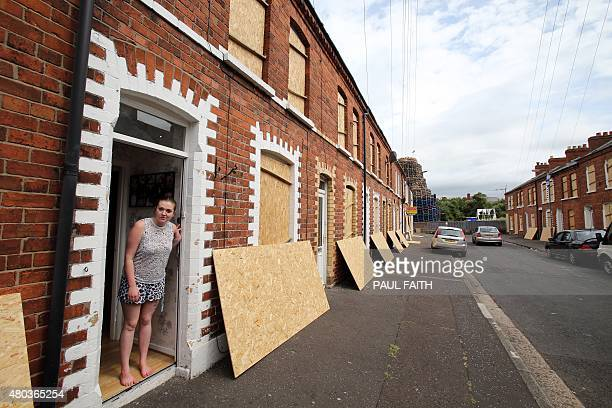 A woman stands in her doorway as houses are evacuated and protected at Clobham Street in east Belfast Northern Ireland as one of the biggest bonfires...