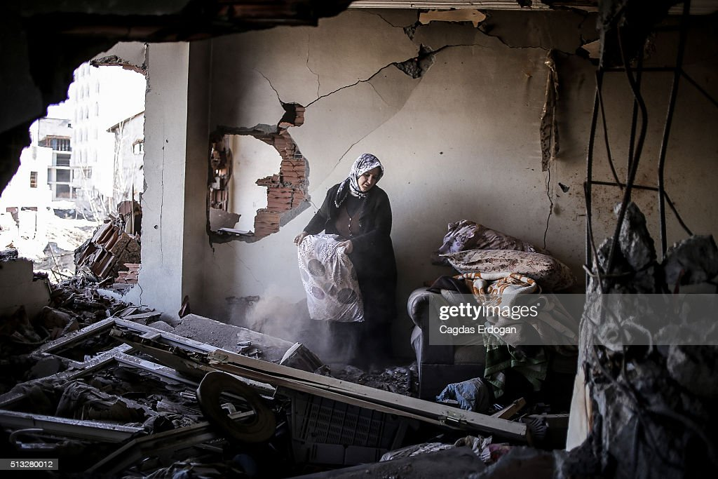 A woman stands in her ruined house as she checks her belongings on March 2, 2016 in Cizre, Turkey. Turkish authorities scaled down a 24-hour curfew imposed on the mainly Kurdish town of Cizre in southeast Turkey, nearly three weeks after declaring the successful conclusion of military operations there. The curfew was lifted at 5 a.m., allowing residents to return to their conflict-stricken neighborhoods for the first time since December 14. But it will remain in effect between 7:30 p.m. and 5 a.m. Residents began trickling back at first light, their vehicles loaded with personal belongings and, in some cases, children.