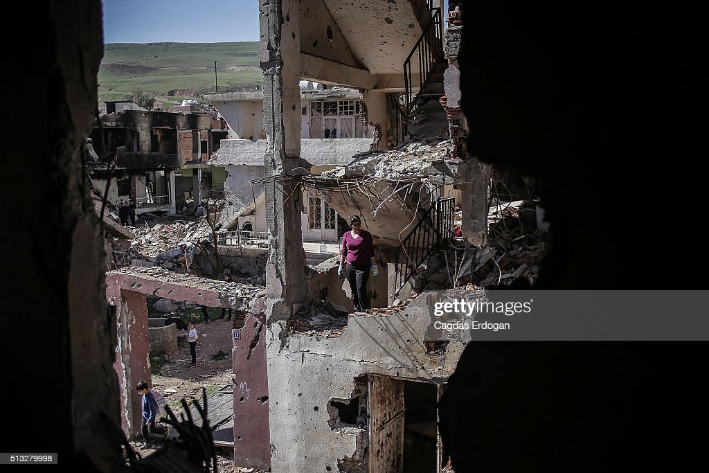 A woman stands in her ruined house on March 2 2016 in Cizre Turkey Turkish authorities scaled down a 24hour curfew imposed on the mainly Kurdish town...