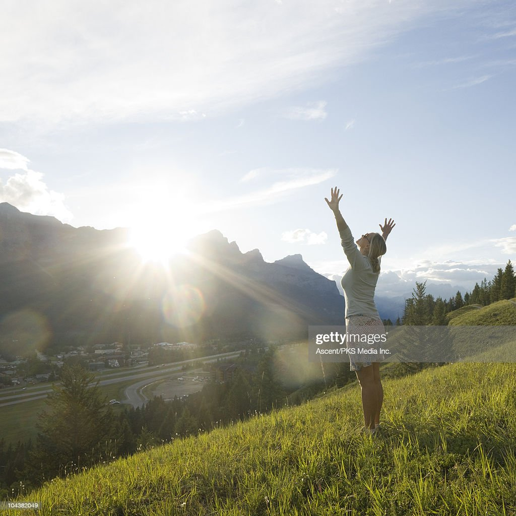 Woman stands in mountain meadow, arms outstretched : Stock Photo