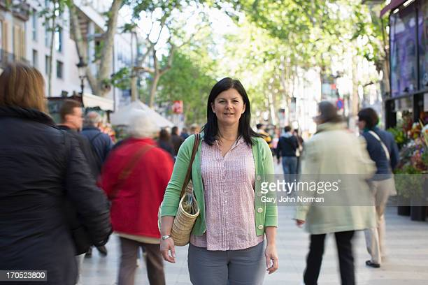 woman stands in street while people walk by