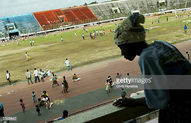 A woman stands in the bleachers of a sports stadium taken over by refugees July 25 2003 in Monrovia Liberia Aid workers warn of a humanitarian...