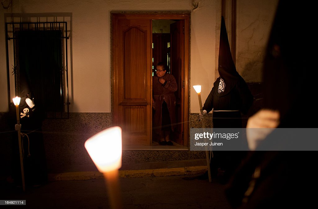 A woman stands in the dooropening of her home looking at penitents of the Cofradia del Santisimo Cristo del Silencio y la Expiracion brotherhood taking part in a holy week procession on March 29, 2013 in Luque near Cordoba, Spain. The origin of this small brotherhood, which uses a skull with crossed shins prominently as their symbol, referring to the mortality and short duration of life but also to the triumph of Jesus over death, dates back to the fifties when a group of young catholic's came up with the idea of forming the brotherhood. Since its founding the brotherhood has a strict penitential character with one of its aims being the public prayer of the Stations of the Cross in the early hours of Good Friday through the streets of this small Andalusian town. Home to the brotherhood is the San Nicolas de Tolentino convent church which was founded in 1626 and dedicated to Our Lady of Grace.