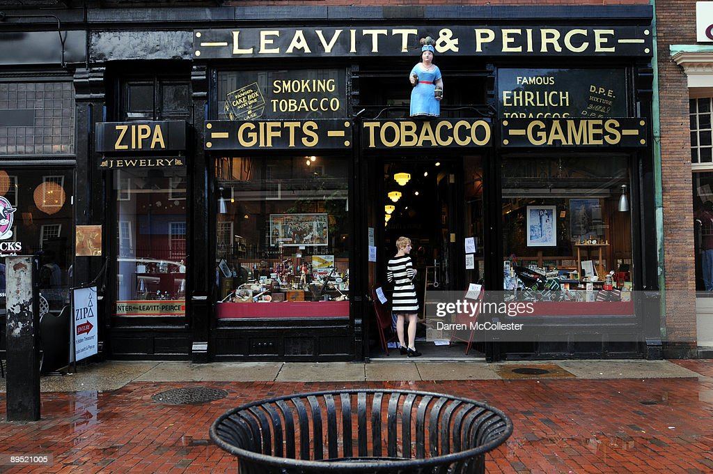 A woman stands in the doorway of Leavitt & Peirce, a famed cigar shop doing business since 1883, in Harvard Square July 30, 2009 in Cambridge, Massachusetts. Harvard Square is a large triangular area located in the heart of Cambridge and adjacent to Harvard University, and is frequented by tens of thousands of tourists a year, and home to thousand of students with MIT University just down the road.