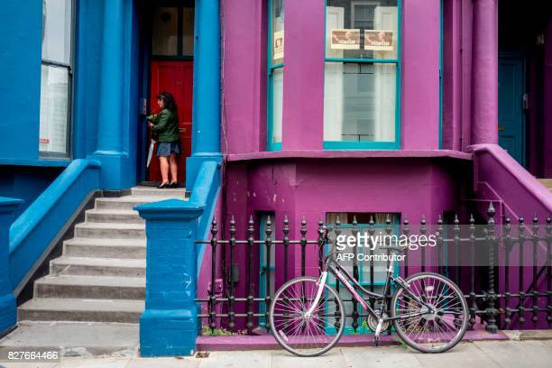 A woman stands in the dorrway of a painted house in the Notting Hill district of west London on August 8 2017 Last week The Bank of England cut its...