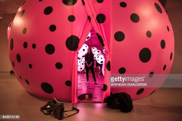A woman stands in the Dots Obsession Love Transformed into Dots room during a preview of the Yayoi Kusama's Infinity Mirrors exhibit at the Hirshhorn...