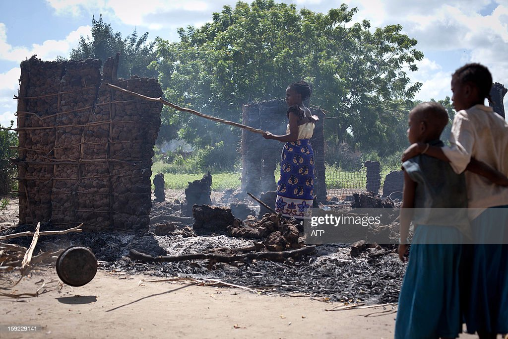 A woman stands in the remains of a burnt house on January 10, 2013 following an overnight attack on the village of Kibusu in the Tana river Delta region. At least 10 people were killed and several wounded in a retaliatory dawn raid Thursday in the Tana River delta region of southeast Kenya, the latest violence to flare up in an area where scores died in clashes last year, Kenya Red Cross said. The attack came a day after nine were killed in a raid. Violence in the region first erupted in August, pitting the Pokomo farming community against their Orma pastoralist neighbours and leading to a series of vicious reprisal killings and attacks that left more than 150 people dead. AFP PHOTO/Ivan LIEMAN