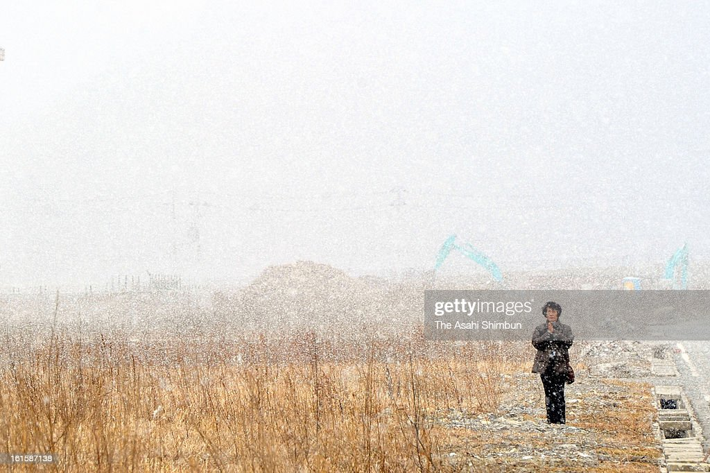 A woman, stands in the snow and prays towards the former city hall on February 11, 2013 in Minamisanriku, Miyagi, Japan. 2 year anniversary approaches though the restoration from the earthquake and tsunami have been delayed.