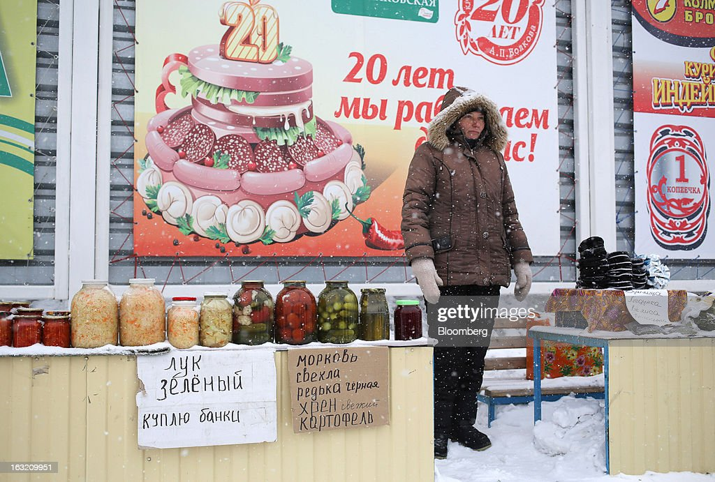 A woman stands in the snow and sells pickled vegetables from a stall outside a Lenta LLC supermarket in Prokopyevsk, Kemerevo region, Russia, on Wednesday, March 6, 2013. Lenta LLC, a Russian hypermarket operator controlled by TPG Capital, is selling its first bond to expand after using company funds for a leveraged buyout by the U.S. firm. Photographer: Andrey Rudakov/Bloomberg via Getty Images
