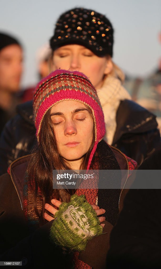 A woman stands in the stone circle as the sun rises, as druids, pagans and revellers take part in a winter solstice ceremony at Stonehenge on December 21, 2012 in Wiltshire, England. Predictions that the world will end today as it marks the end of a 5,125-year-long cycle in the ancient Maya calendar, encouraged a larger than normal crowd to gather at the famous historic stone circle to celebrate the sunrise closest to the Winter Solstice, the shortest day of the year.