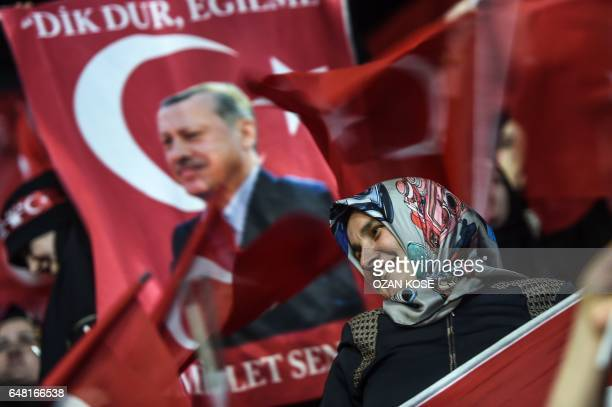 TOPSHOT A woman stands near a flag bearing a Turkish President Recep Tayyip Erdogan's picture on March 5 2017 in Istanbul during a progovernment...
