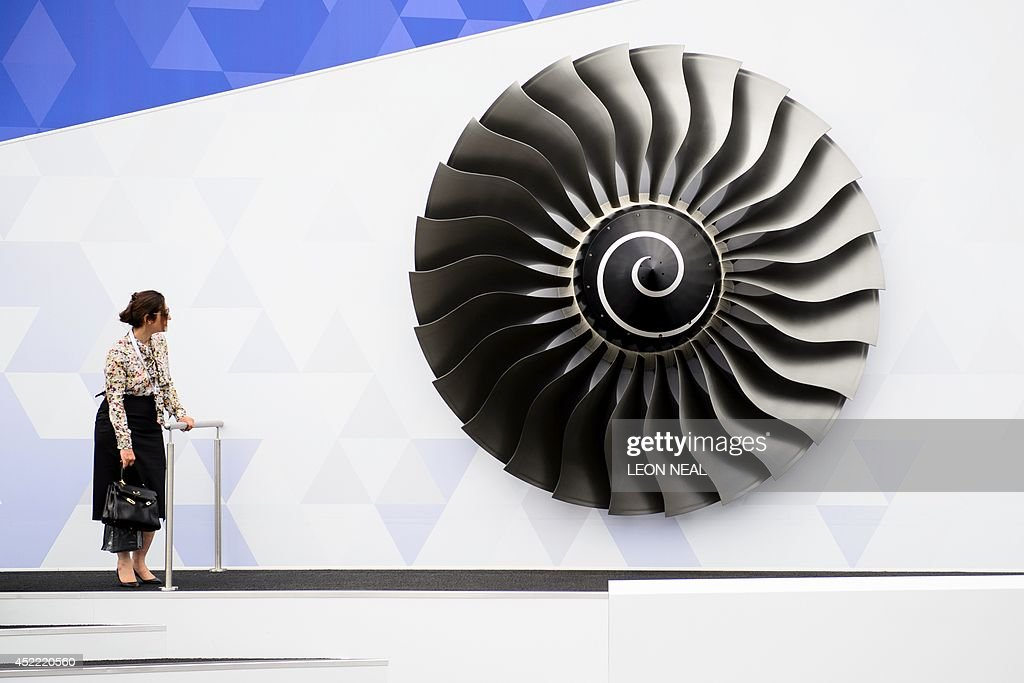 A woman stands near a model of a Rolls Royce Trent engine at the Farnborough Air Show in Hampshire, southern England, on July 16, 2014. AFP PHOTO / LEON NEAL