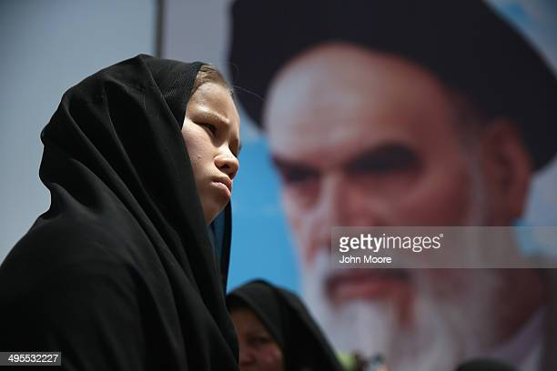 A woman stands near a portrait of the Ayatollah Khomeini outside Khomeini's shrine on the 25th anniversary of his death on June 4 2014 on the...