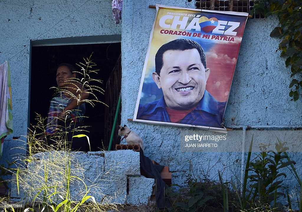 A woman stands near a poster of Venezuelan President Hugo Chavez in Caracas, on January 2, 2013. Chavez is conscious and fully aware of how 'complex' his condition remains three weeks after difficult cancer surgery in Havana, the Venezuelan president's handpicked successor, Vice President Nicolas Maduro, said Tuesday. Chavez underwent his fourth cancer-related surgery three weeks ago in Havana and has been bed-ridden ever since. AFP PHOTO/JUAN BARRETO
