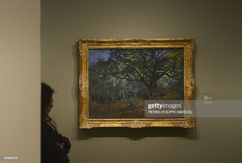 A woman stands near a work by Claude Monet entitled 'The Bodmer oak, Fontainebleau forest' at the Thyssen Bornemisza museum in Madrid on February 4, 2013, during the exhibition 'Impressionism and Open-air Painting. From Corot to Van Gogh'.