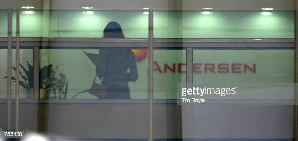 A woman stands near an Andersen sign April 1 2002 in the building that houses the main offices of Arthur Andersen LLP in Chicago Two companies that...