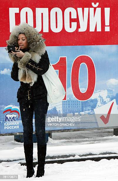 A woman stands near an election poster for the proKremlin United Russia party in central Moscow 30 November 2007 Campaigning in Russia's...