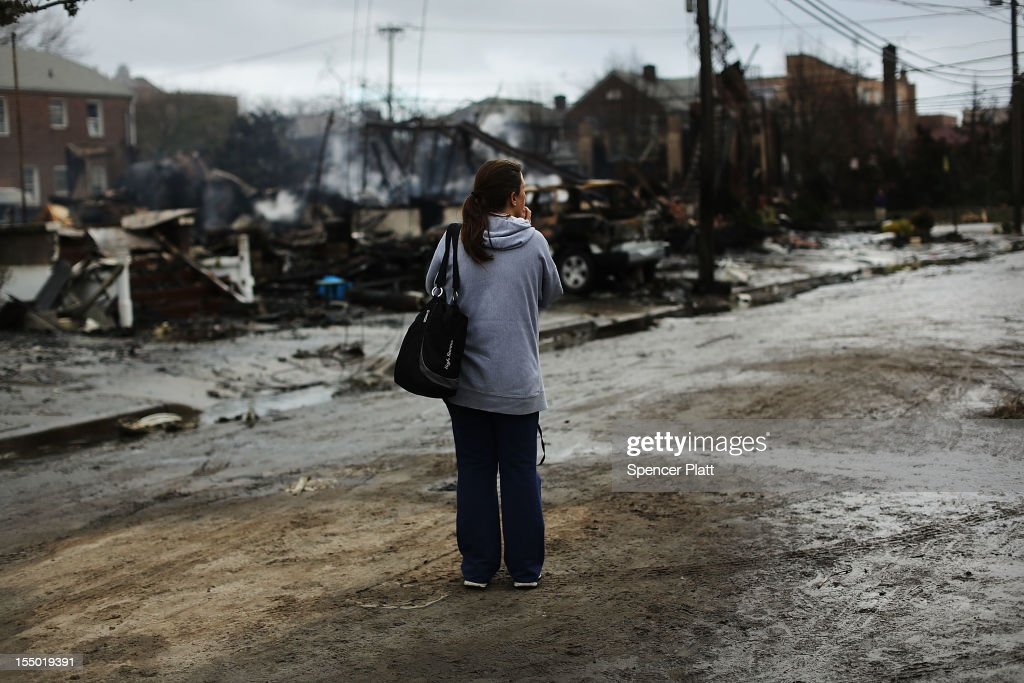 A woman stands near destroyed homes after Hurricane Sandy on October 30, 2012 in the Rockaway section of the Queens borough of New York City. At least 40 people were reportedly killed in the U.S. by Sandy as millions of people in the eastern United States have awoken to widespread power outages, flooded homes and downed trees. New York City was hit especially hard with wide spread power outages and significant flooding in parts of the city.