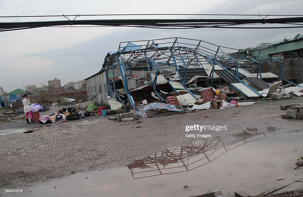 A woman stands next to a collapsed building on March 20, 2013 in Dongguan, China. Nine people have been killed and about 272 others injured after a thundersand hailstorm swept Dongguan city on Wednesday afternoon.