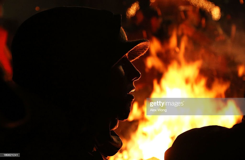 A woman stands next to a fire to keep herself warm during the 127th Groundhog Day Celebration at Gobbler's Knob on February 2, 2013 in Punxsutawney, Pennsylvania. Thousands of people gathered at the event to watch Phil's annual forecast.
