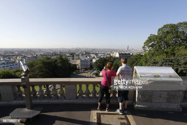A woman stands next to a man as she takes pictures on the deserted Butte Montmartre near the SacreCoeur Basilica in Paris on August 9 2016 Many...
