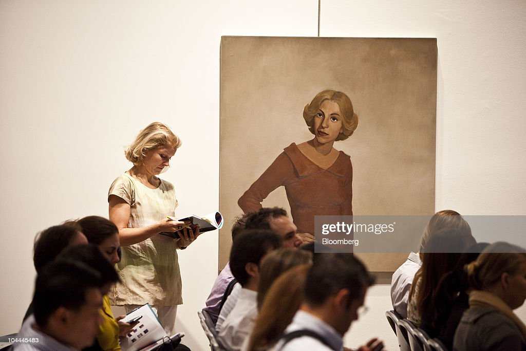 A woman stands next to a painting by John Currin titled 'Shakespeare Actress' during an auction of Lehman Brother's artwork collection at Sotheby's in New York, U.S., on Saturday, Sept. 25, 2010. Artworks being auctioned from the collection of Lehman Brothers Holdings Inc. may raise another $16 million for its creditors as collectors and souvenir hunters snap up remains of the collapsed bank. Photographer: Ramin Talaie/Bloomberg via Getty Images