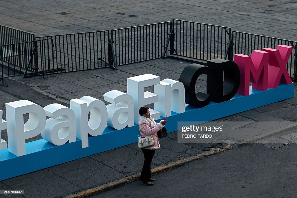 A woman stands next to a sign announcing the visit of Pope Francis to Mexico City, in the Mexican capital on February 12, 2016 hours before the arrival of the pontiff to the country. Pope Francis left Rome on Friday bound for Cuba, where he is to hold a historic meeting Russian Patriarch Kirill before continuing on to Mexico for a five-day visit. AFP PHOTO / Pedro PARDO / AFP / Pedro PARDO