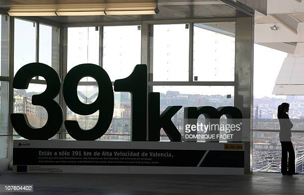 A woman stands next to an advertising for the Spanish highspeed train's track connecting Madrid to Valencia at the train station of Atocha of Madrid...