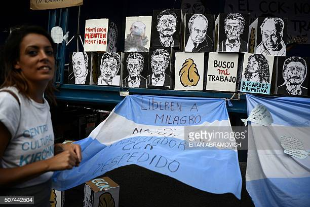 A woman stands next to an Argentinian flag reading 'Liberate Milagro' and caricatures of Argentinian President Mauricio Macri during a protest of...