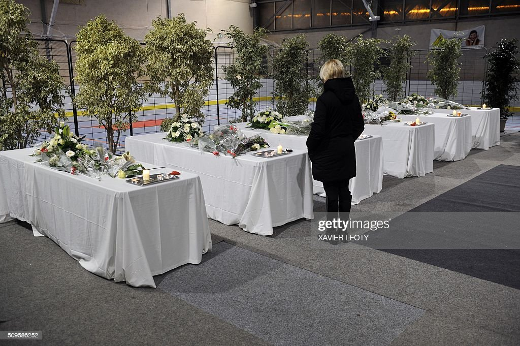A woman stands next to candles and flowers put on six tables representing coffins in Rochefort, on February 11, 2016, in tribute to the victims of the road accident between a school bus and a truck, killing at least six children. The head-on smash with a lorry carrying rubble came around 7:15 am (0615 GMT) in Rochefort in the western Charente-Maritime region. The school bus was carrying about 17 people, and three children suffered minor injuries in the accident, a police source said. / AFP / XAVIER LEOTY
