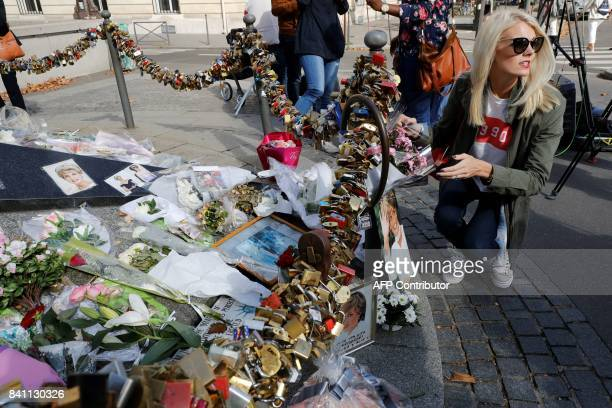 A woman stands next to flowers messages pictures and locks laid around the Flame of Liberty monument which became an unofficial memorial for Diana...