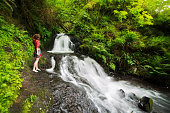 Woman stands next to forest waterfall barefoot