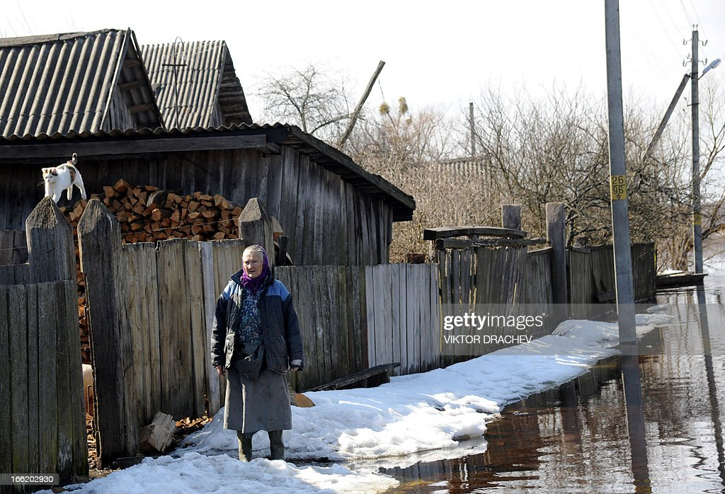 A woman stands next to her house during spring flood in a village of Snyadin some 300 km south of Minsk, on April 9, 2013. Belarus will take all necessary precautions to minimize the consequences of spring floods, Belarus President Alexander Lukashenko said as he visited Minsk-based Sukno Company on 5 April.
