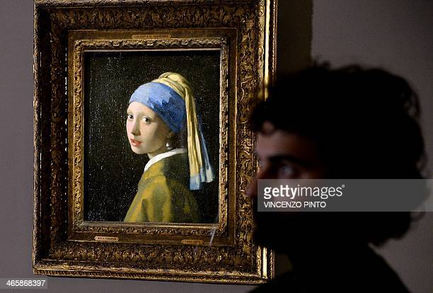 A woman stands next to the masterpiece 'Girl with a Pearl Earring' by Dutch painter Johannes Vermeer during a preview of the exhibition 'The Myth of...