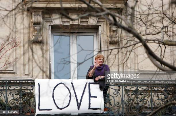 A woman stands on a balcony behind a banner reading 'Love' during a Unity rally Marche Republicaine on January 11 2015 in Paris in tribute to the 17...
