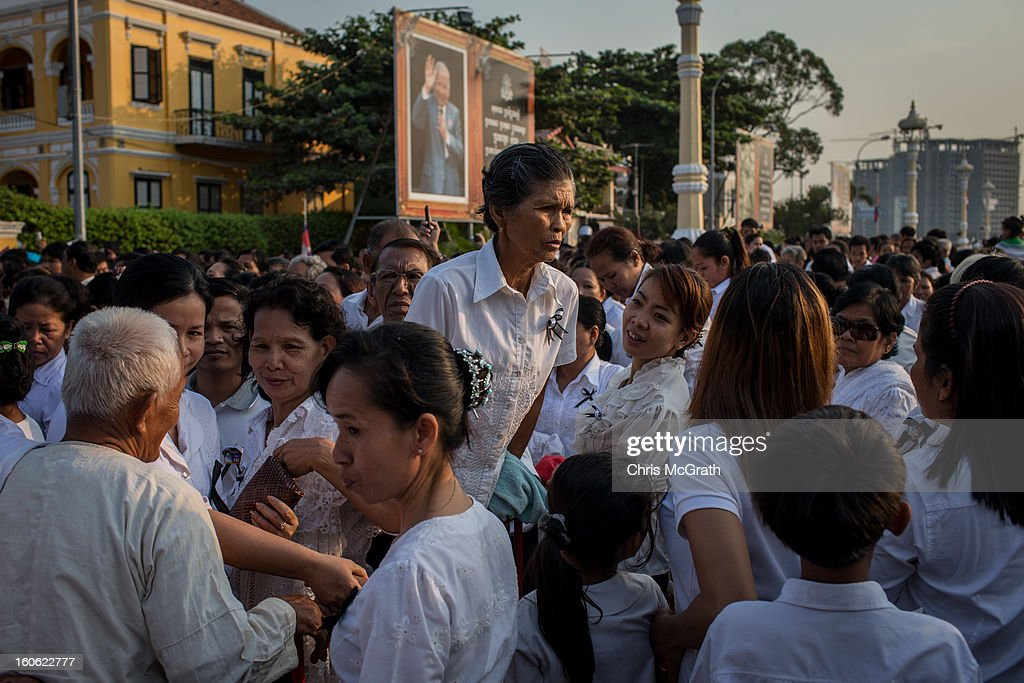 A woman stands on a barricade amongst hundreds of mourners pushing to get to the front of the line to enter the cremation site to pay their final respects to former King Norodom Sihanouk ahead of tonight's cremation on February 4, 2013 in Phnom Penh, Cambodia. The former kings coffin was transported to the cremation site after being paraded through the capital in a lavish funeral procession. The cremation will take place on Monday evening the funeral pyre will be lit by his wife and son King Norodom Sihamoni.