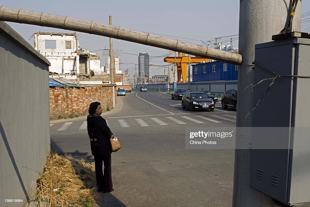 A woman stands on a road at the North Bund on February 19, 2012 in Shanghai, China. According to local media, the North Bund area will be reconstructed as a international shipping and financial zone, a modern commercial and high-end residential area, and recreation center.