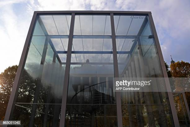 A woman stands on a staircase in a glass cube containing an olfactory cloud Le Nuage Parfumé or OSNI 1 launched by Cartier and displayed outside the...