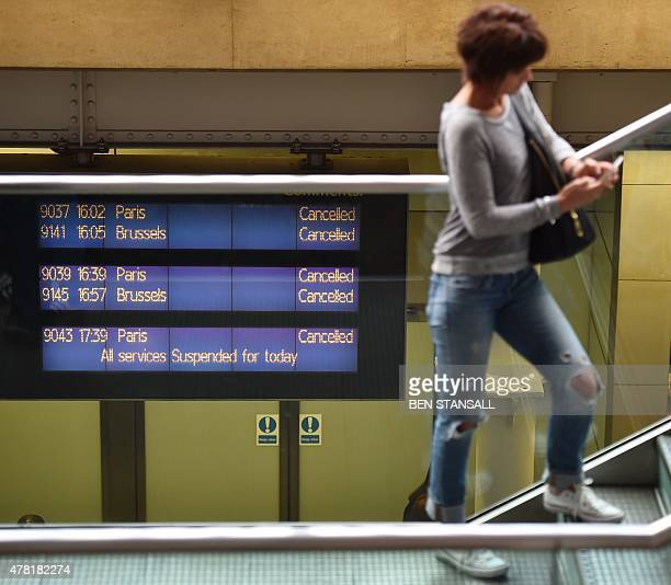 A woman stands on a staircase in front of the arrivals board that is showing all services cancelled at the Eurostar terminal at St Pancras station in...