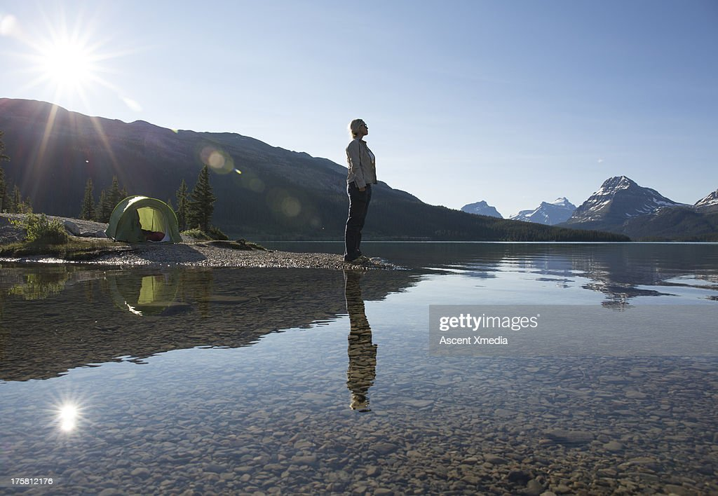 Woman stands on beach beside tent, looks out : Stock Photo