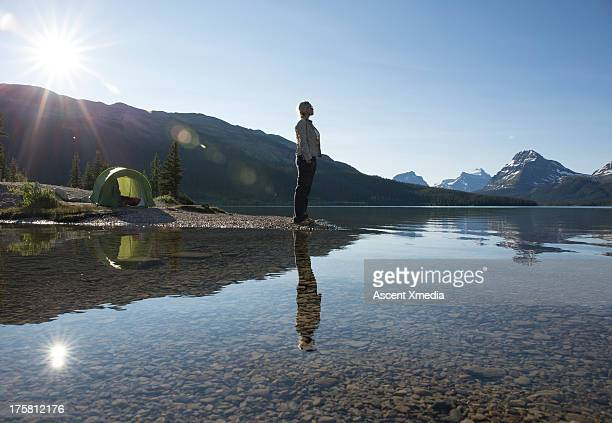Woman stands on beach beside tent, looks out