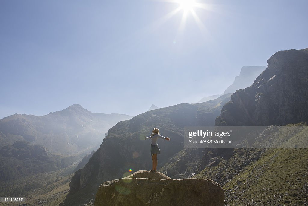 Woman stands on boulder, arms outstretched : Stock Photo