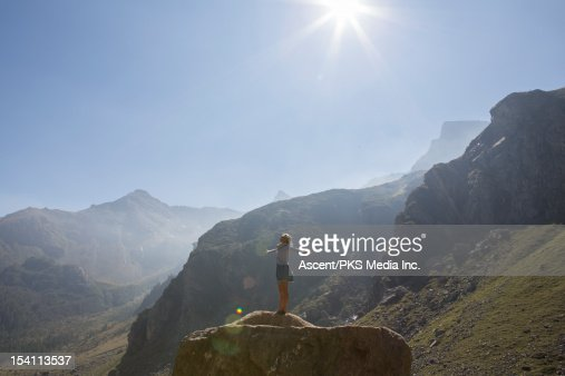 Woman stands on boulder, arms outstretched : Stock-Foto