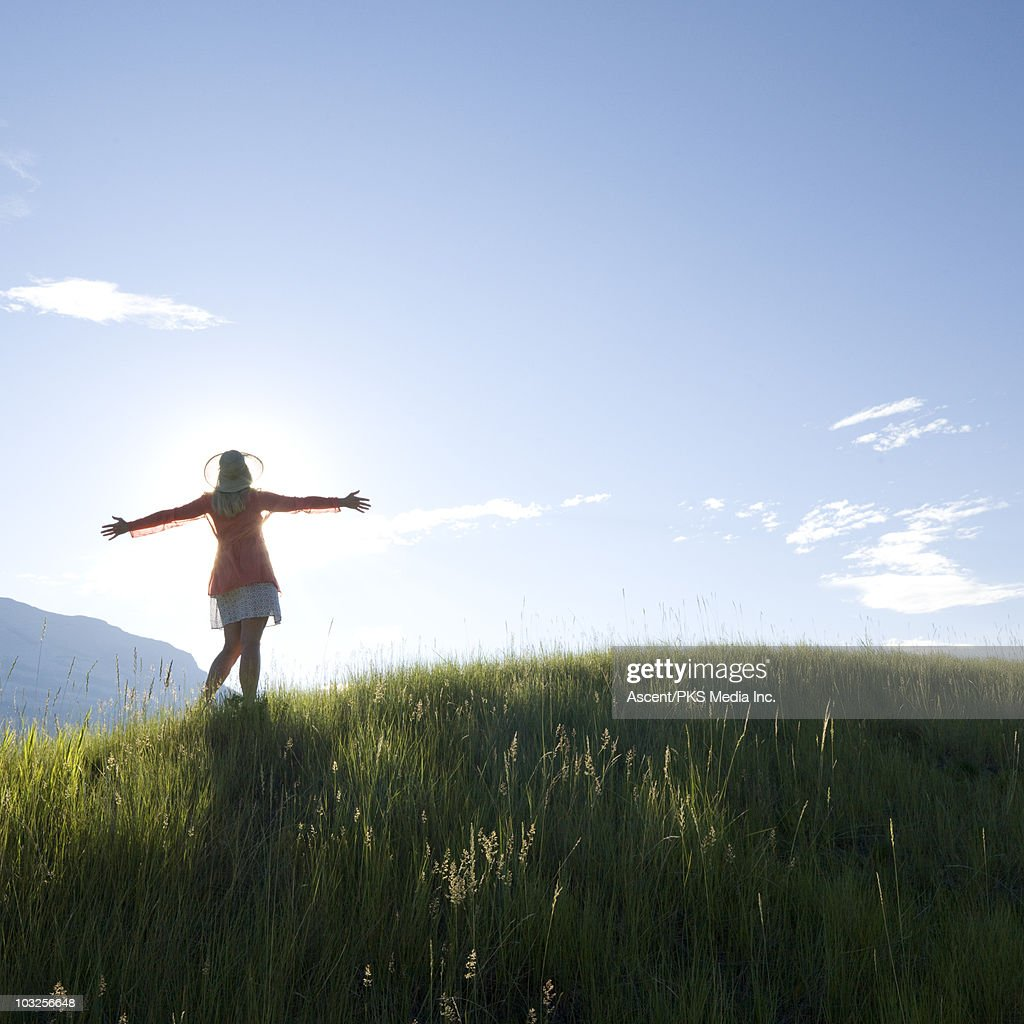 Woman stands on grassy knoll above mtns, arms out