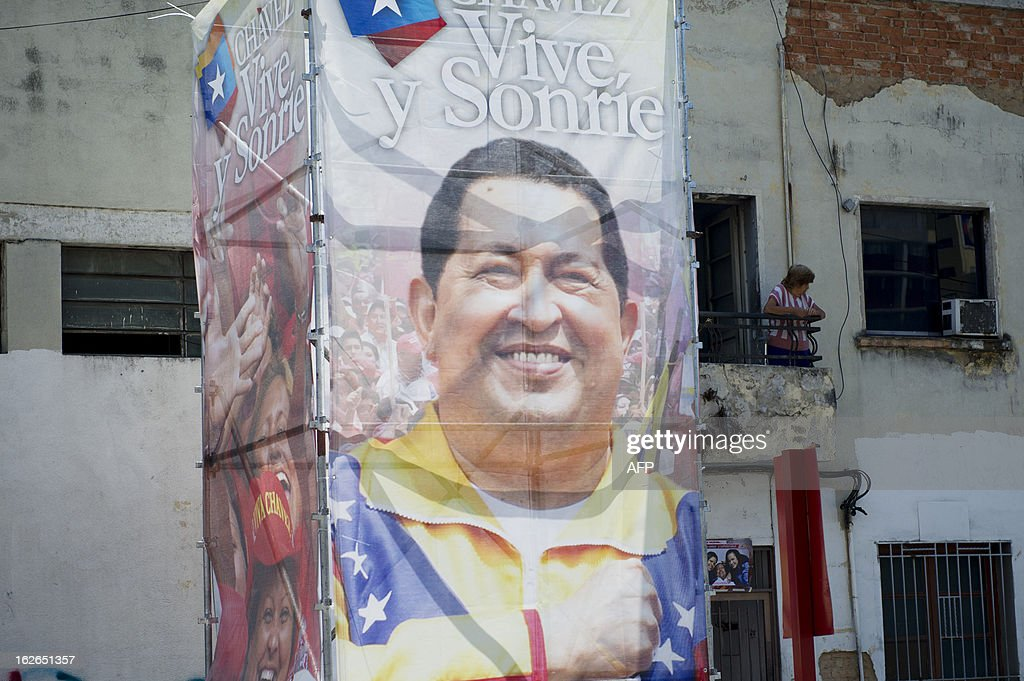 A woman stands on her balcony next to a poster of Venezuelan President Hugo Chavez, in front of the military hospital, where Venezuelan President Hugo Chavez has been hospitalized following his return from Cuba, in Caracas, on February 25, 2013. The mystery surrounding the president's health has cast doubt over the political future of a nation sitting on top of the world's biggest oil reserve. AFP PHOTO/Leo RAMIREZ
