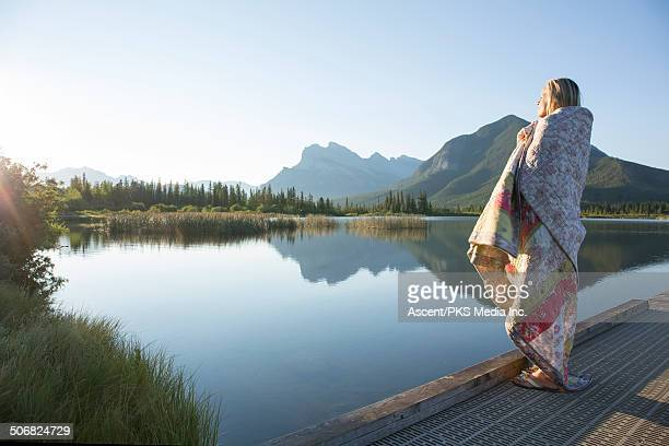 Woman stands on mountain dock, wrapped in blanket
